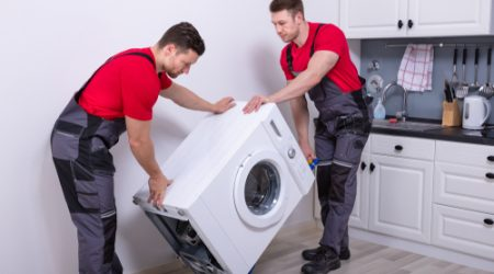 Two,Young,Male,Professional,Movers,In,Uniform,Placing,The,Modern
